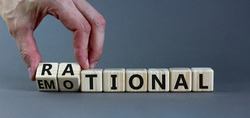 Rational or emotional symbol. Psychologist turns wooden cubes and changed the word 'rational' to 'emotional'. Beautiful grey background. Psychological and rational or emotional concept. Copy space.