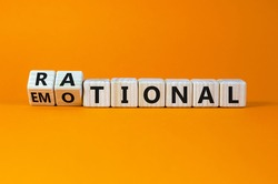 Rational or emotional symbol. Turned wooden cubes and changed the word 'rational' to 'emotional'. Beautiful orange background. Psychological and rational or emotional concept. Copy space.
