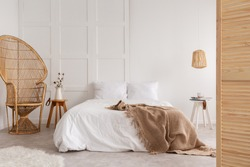 Rattan chair and wooden table next to bed with brown blanket in white bedroom interior. Real photo
