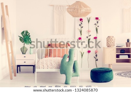 Rattan chandelier above single metal bed with pattered duvet in boho bedroom interior with natural furniture and flower board #1324085870