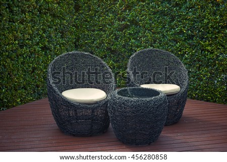 Rattan garden table and chairs with water resistant outdoor. Patio furniture in a beautiful garden. #456280858