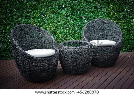 Rattan garden table and chairs with water resistant outdoor. Patio furniture in a beautiful garden. #456280870