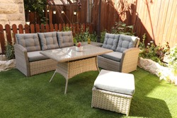 rattan sofas, plastic and wood, in an old green garden