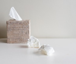 Rattan tissue box and crumpled tissues on table - cold and flu season concept, grief, concept (selective focus)