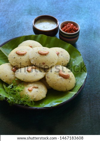 Rava idli : Indian vegetarian steamed breakfast served with chutney and chutney powder in the background. Decorated with cashews served on banana leaf.