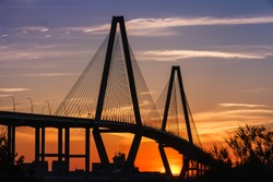 Ravenel Bridge silhouette, a cable-stay bridge outlined against the evening sky at sunset near Charleston, South Carolina.