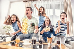 Raving fans cheering sports, as family of five watch football, or ice-hockey match on the TV at home, screaming from joy.
