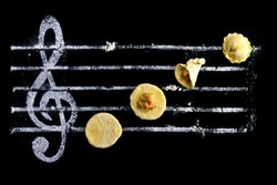 Ravioli - cooking music concept. Dough with minced meat on a black background and a treble clef from flour