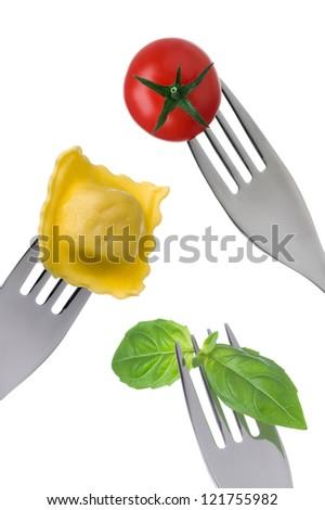ravioli pasta basil and cherry tomato on forks against white background