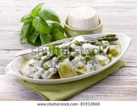 ravioli stuffed with ricotta and basil garnish with cream and asparagus