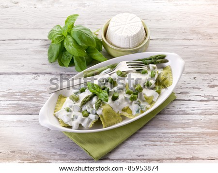 ravioli stuffed with ricotta and basil garnish with cream and asparagus
