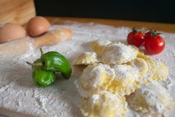 Ravioli / Tortellini uncooked,with fresh paprika tomatoes and two eggs  on floured wood table.black and wood background.Healthy food concept