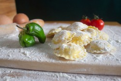 Ravioli / Tortellini uncooked,with fresh paprika tomatoes and two eggs  on floured wood table.wood black background.Healthy food concept