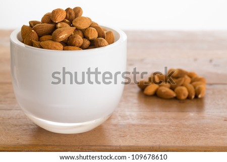 Raw almond nuts in white glass bowl on old wooden table