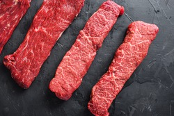 Raw, alternative beef steaks flap flank Steak, machete steak or skirt cut, Top blade or flat iron beef and tri tip, triangle roast with denver cut . Black stone background. Top view.