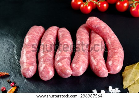 Raw and fresh meat. Fresh sausages and chicken meat ready to cook. Black slate background. Butchers\' meat.