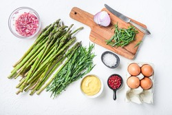 Raw asparagus eggs and french dressing ingredients with dijon mustard, onion chopped in red vinegar taragon on white textured background, top view.