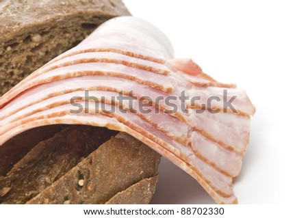 Raw bacon with bread over white background