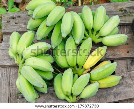 raw banana lay down on wooden plate