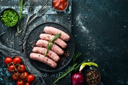 Raw barbecue sausages with spices and vegetables. Top view. Free space for your text.