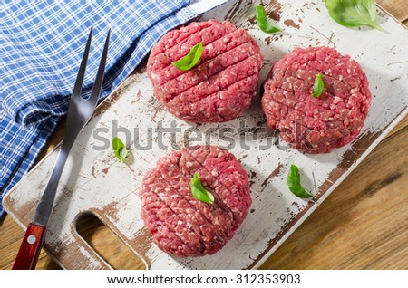 Raw beef burger patties on a old cutting board. Top view #312353903