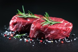 Raw beef fillet steaks with herbs and spices on on dark background