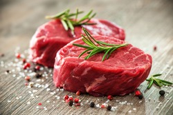 Raw beef fillet steaks with spices on wooden background