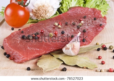 Raw beef frying steak on chopping board with vegetables
