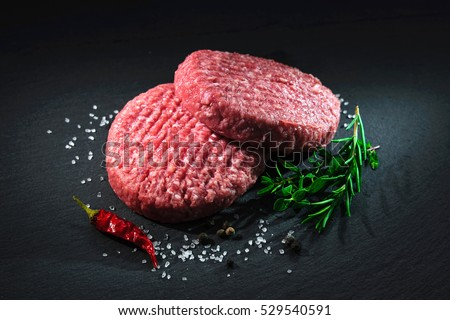 Raw beef hamburger patties with spices on dark slate plate #529540591