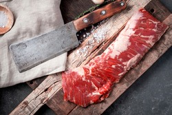 Raw beef machete steak with meat axe on a wooden Board with seasoning. Stone background.