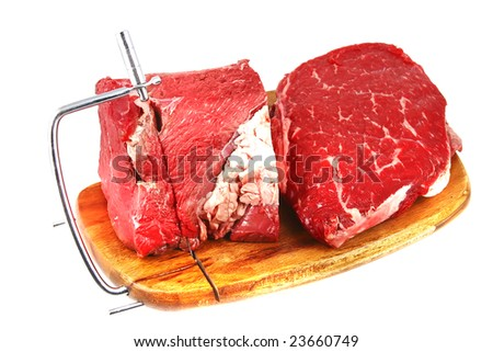 raw beef meat chunk and slices on cutting plate over white
