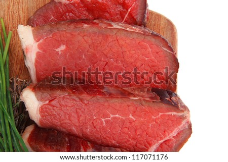 raw beef meat fillet on wooden plate with thyme and chives isolated on white background