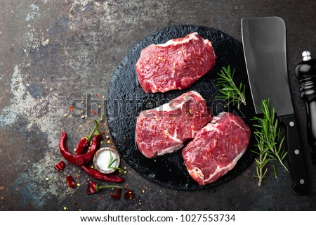 Raw beef meat. Fresh steaks on slate board on black background. Top view