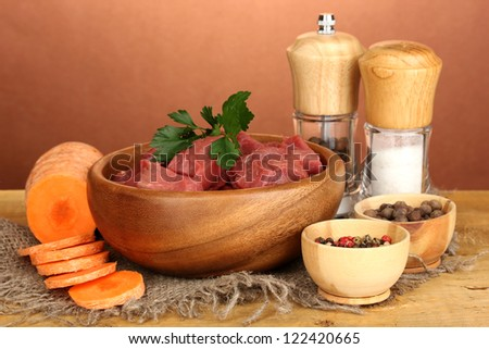 Raw beef meat marinated with herbs and spices on wooden table on brown background