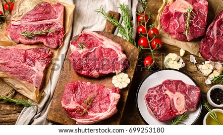 Raw beef meat on a dark wooden board. Top view #699253180