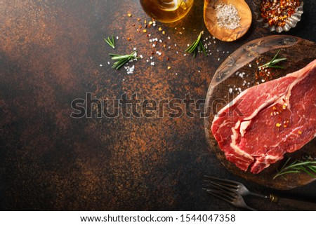 Raw beef meat on table with ingredients for cooking. Cooking background. Cooking concept. Horizontal