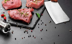 Raw beef meat with butcher knife on slate plate.Scattered black pepper, chili .Dark bakcground.Selective focus . copy space
