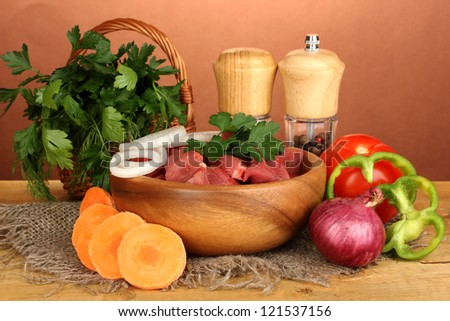 Raw beef meat with herbs and spices on wooden table on brown background