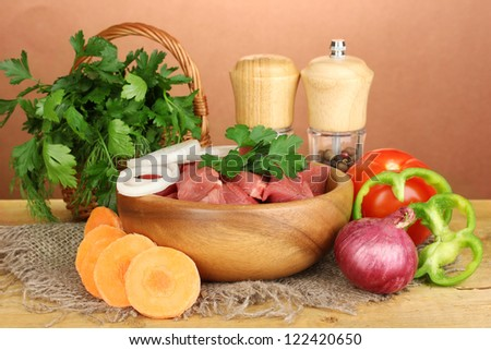 Raw beef meat with herbs and spices on wooden table on brown background - stock photo