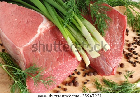 Raw beef meat with spice, fennel and leek on wooden board