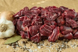 Raw beef meat with spices on paper