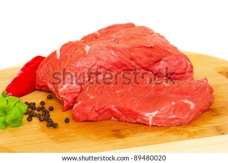 raw beef meat with spices on wooden board over white