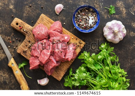 Raw beef pieces on a wooden Board with spices. The view from the top,flat lay