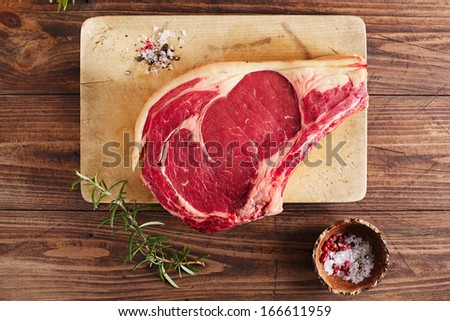 raw beef Rib bone steak on wooden board and table with spices