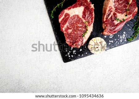 Raw beef steak and ingredients on cutting board. Raw meat on white concrete background. Top view. Copy space