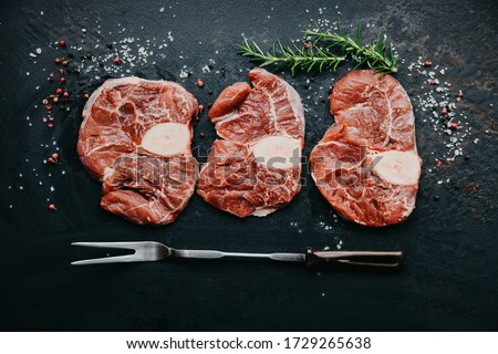 Raw beef steak osso bucco with herbs and spices on dark table. Marble meat. Top view and copy space Foto stock ©