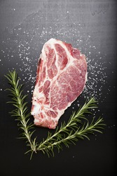 Raw beef steak with rosemary and red onion on dark wooden background