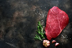 Raw beef steak with spices on a dark slate, stone or concrete background. Top view with copy space.