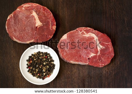 Raw beef steaks and peppercorns on wooden board.  Overhead view.
