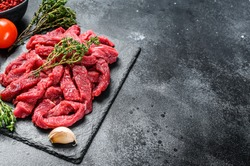 Raw beef Stroganoff meat. Black background. Top view. Copy space